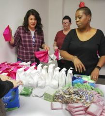"Roxanna Pena of Upland, Alexia Madigan of Temple City and Ehmandah Ramsey of San Dimas put together bags of feminine products March 17 at the She Stories headquarters in Claremont. Ramsey, owner of women's empowerment organization She Stories, hosts monthly ""Period Parties"" where volunteers pack bags of pads, tampons and cleansing wipes with a hand-written, encouraging note for women in local homeless shelters. Items were donated by the 16 women who packed the items, their respective churches and Target. / photo by Natasha Brennan"