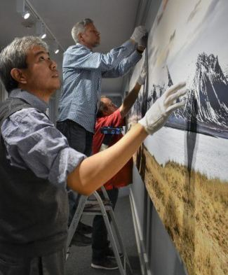 "Art Suwansang, senior adjunct professor of photography, photography department manager Kevin Bowman and senior adjunct professor of photography David Bess install a panorama piece for the Carlson Gallery exhibit, ""Capture and the Seamless Stream."" The landscape, made in Iceland by Suwansang, is nearly 4 feet tall, 20 feet wide and took five people to install. / photo by Natasha Brennan"
