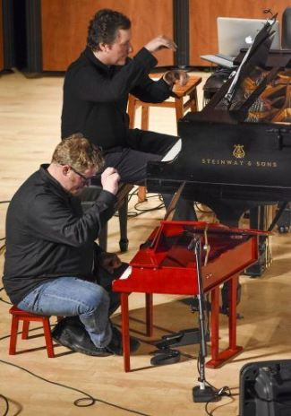 "University of La Verne artist-in-residence Rafael Liebich, on the Steinway piano, and Grammy nominated pianist Aron Kallay, on the toy piano, play ""Man on Wiire,"" by Isaac Schankler at the ""Piano(+)"" concert Saturday in Morgan Auditorium. The piece is performed using an accelerometer on a Nintendo Wii controller to adjust the piano's tone. The performance included seven pieces using pianos, recorded electronic melodies and video installations. / photo by Natasha Brennan"