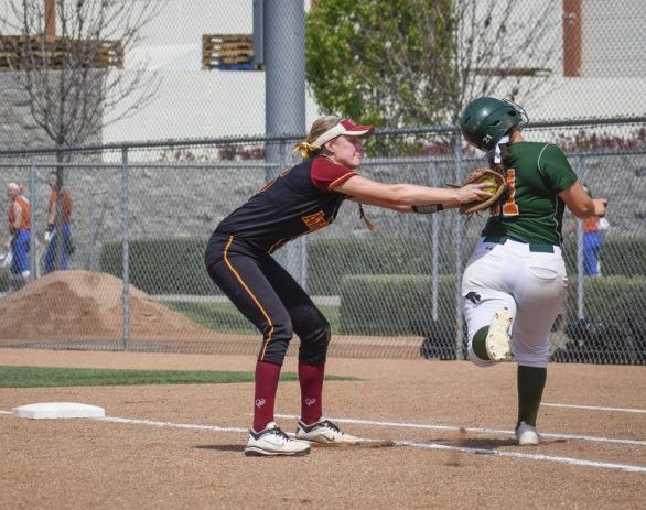 La Verne sophomore first baseman Katheryn Navarro narrowly avoids a tag by Claremont-Mudd-Scripps senior first baseman Briana Halle during the fourth inning of the first SCIAC Postseason Tournament game Friday. The Leopards fell to the Athenas, 2-0. / photo by Natasha Brennan
