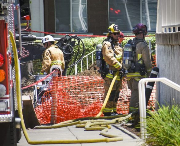 Firefighters work to contain a gas leak that caused an emergency evacuation of the Oaks dorms, Barkley Building, Leo Hall and the Arts and Communication building Monday afternoon. The gas line was hit during construction on a fire hydrant on the north side of Oaks A building. Students were asked to stay out of their dorms for three hours and cars in the surrounding parking lots were also inaccessible as starting the ignition could trigger an explosion. / photo by Natasha Brennan